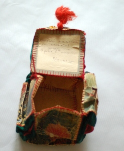 Jewelry box made by Tsipora and Bena as a gift for the International Women's day on March 8, 1958. The wishes are written on the inside of the lid. The box is made from postcards and satin inserts in the corners; the handle is a tassel fashioned from silky threads.