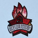 "Pin, the way it looked in the beginning of the 1950s, worn by each Pioneer, a member of the Communist Youth organization for children aged 9 to 14. The words say ""Always ready!"" (Photo from https://ru.wikipedia.org/wiki/пионерский_значок)"